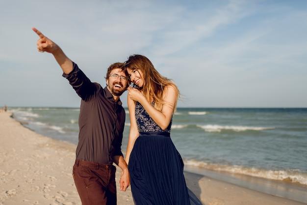 Элегантная влюбленная пара, идущая на солнечном пляже. романтическое настроение. девушка в элегантном синем платье с блестками. ее муж на что-то указывает.