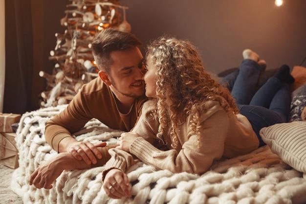 クリスマスツリーの近くに家で座っているエレガントなカップル
