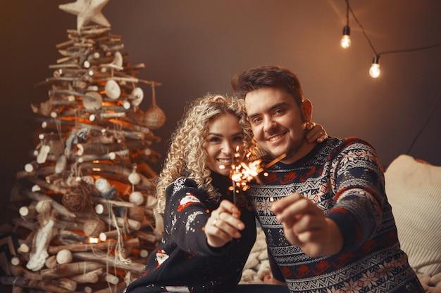 크리스마스 트리 근처 집에 앉아 우아한 커플