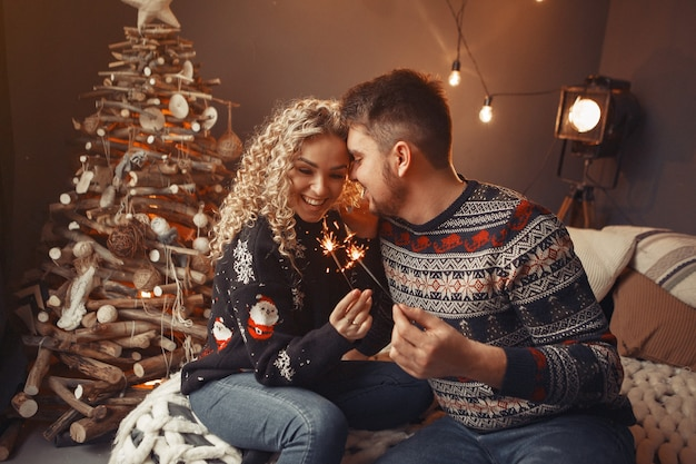 Элегантная пара сидит дома возле елки