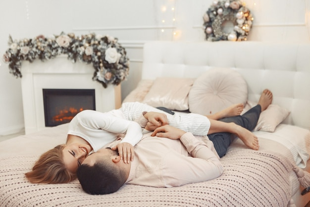 Elegant couple sitting on a bed in a christmas decorations