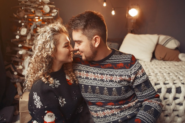 Elegant couple sitting at home near christmas tree