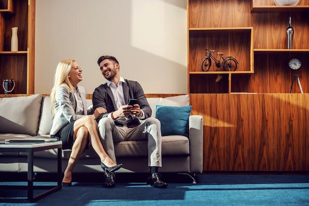 Элегантная пара, сидя в офисе утром и смеясь. привлекательный мужчина показал что-то забавное по мобильному телефону, а затем женщина засмеялась, взяв его за руку. цель отношений