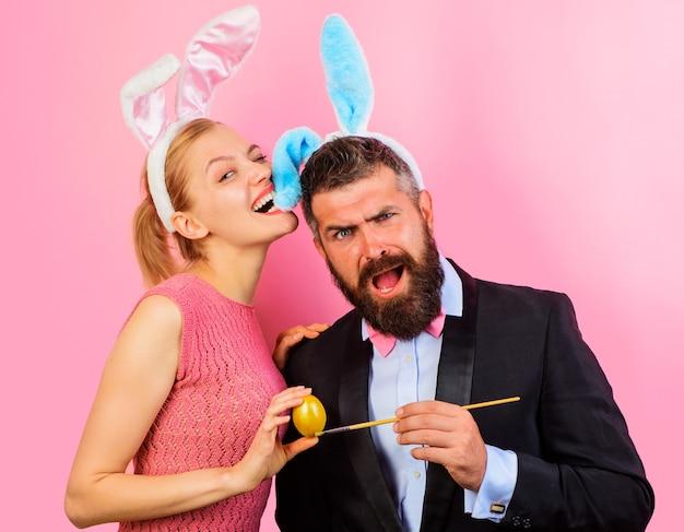 Элегантная пара с кроличьими ушами рисует пасхальное яйцо на розовом фоне.