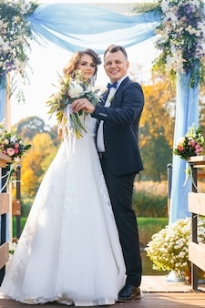 Элегантная кудрявая невеста и счастливый жених на открытом воздухе на фоне озера. креативная стильная свадебная церемония