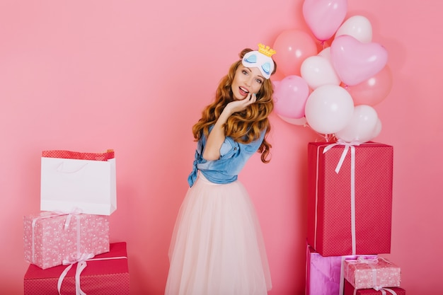 Elegant curly girl in lush trendy skirt is surprised by number of gifts for her birthday from friends. charming long-haired young woman in sleep mask posing with presents and helium balloons at party