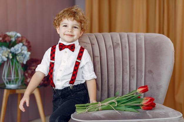 Элегантный милый маленький мальчик с букетом тюльпанов