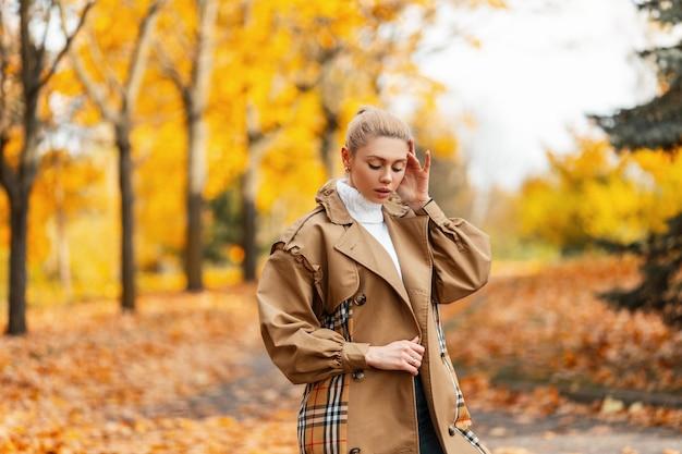 トレンディな髪型のポーズでスタイリッシュなコートを着たエレガントなかわいい若い女性