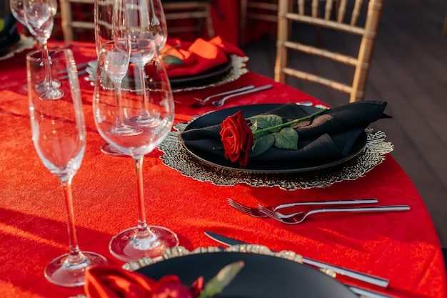 Elegant dinner decor tablecloth plates with napkins and fresh roses glasses cutlery in red color