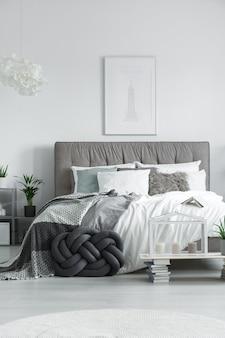 Элегантная двуспальная кровать с различными подушками и набором свечей на небольшом столике из книг.