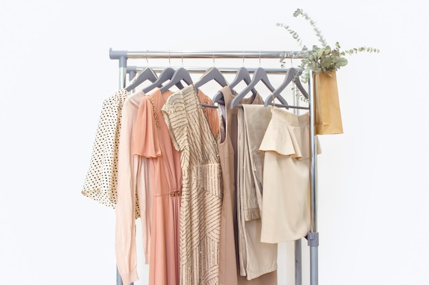 Elegant dress, jumper, trousers and other fashion outfit pastel beige color. spring cleaning home wardrobe.