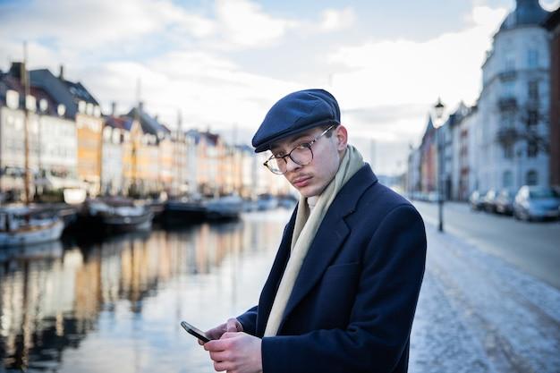 Элегантно одетый бизнесмен проверяет свой телефон, пока его нет дома