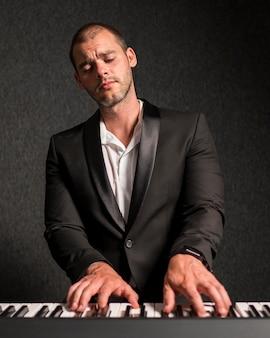 エレガントな服を着たミュージシャンがキーボードミディアムショットを演奏