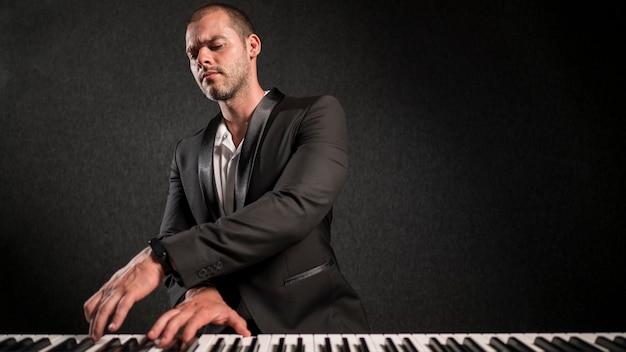 エレガントな服を着たミュージシャンがキーボードを演奏