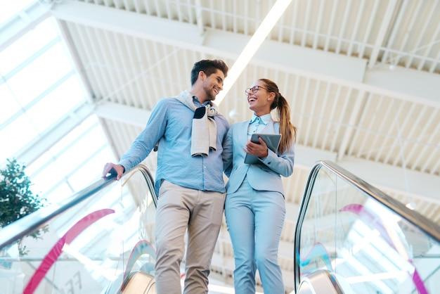 Элегантно одетые улыбающиеся пара обниматься и спускаясь по эскалатору.