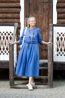Элегантная пожилая женщина в голубом платье спускается по лестнице с крыльца старого бревенчатого дома