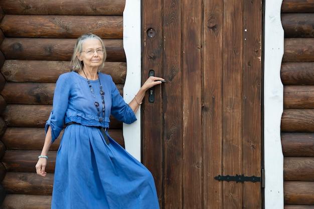 Элегантная пожилая женщина в синем платье стоит у двери старого бревенчатого дома