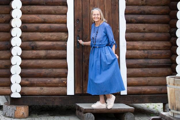 Элегантная пожилая женщина в синем платье стоит на пороге у двери старого бревенчатого дома