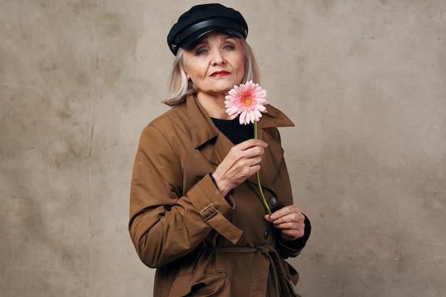 Элегантная пожилая женщина в пальто держит цветочную моду