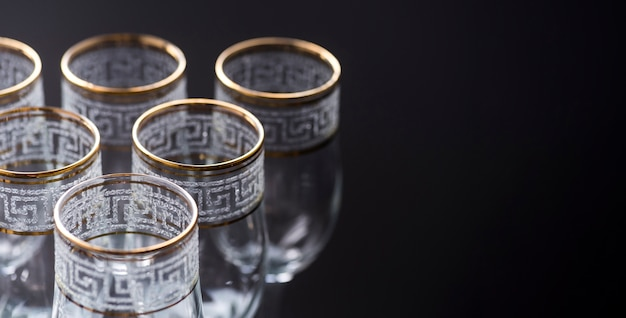 Elegant empty transparent glasses on black backdrop