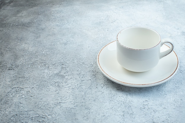 苦しめられた表面を持つ孤立した灰色の表面の左側にあるエレガントな空の白いカップとソース