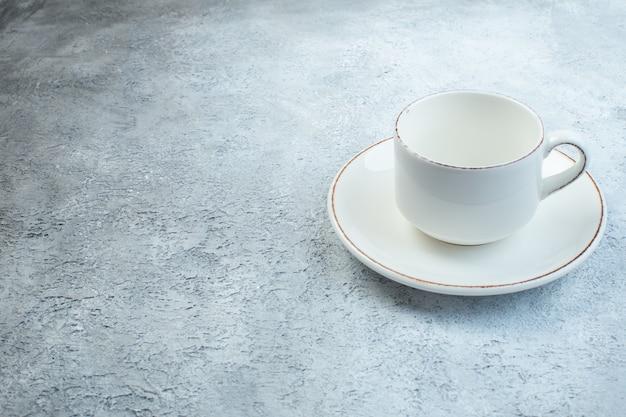 Elegante tazza bianca vuota e salsa sul lato sinistro su superficie grigia isolata con superficie angosciata