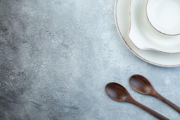 Elegant empty white set for dinner and wooden spoons on the left side on isolated gray surface with free space