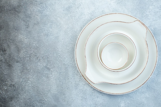여유 공간이있는 격리 된 회색 표면의 왼쪽에 저녁 식사를위한 우아한 빈 흰색 세트