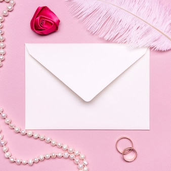 Elegant envelope surrounded by pearls and wedding rings