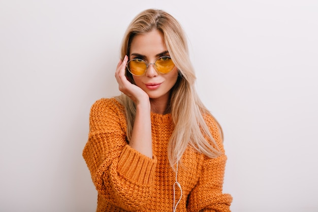 Elegant european lady in vintage yellow sunglasses looking with interest isolated on white background