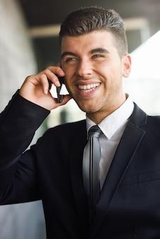 Элегантный исполнительной смеется во время разговора по телефону