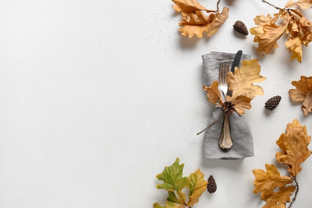 白いテーブルの上のフレームとカトラリーとしてエレガントな秋のオークの葉