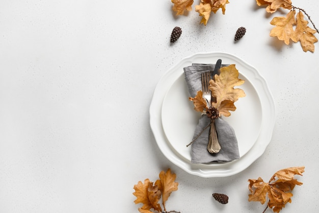 コピースペースと白の乾燥した葉と白いプレートとエレガントな秋のテーブルの設定