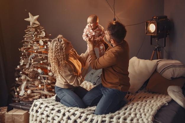 クリスマスツリーの近くに家に座っているエレガントな家族
