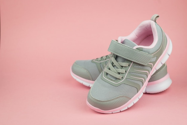 Elegant fashion gray sneakers on pink background. sports shoes. color trend.