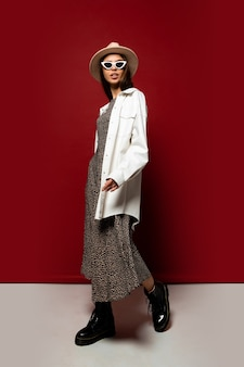 흰색 재킷과 드레스 포즈에 우아한 유행 여자. 블랙 가죽 앵클 부츠. 전체 길이.