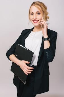 Элегантная модная молодая офисная женщина в костюме, держа папку, разговаривает по изолированному телефону. веселое настроение, успех, карьера, занятость, работа, настоящие положительные эмоции