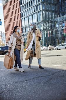 通りを歩いている医療マスクのエレガントな女性の友人