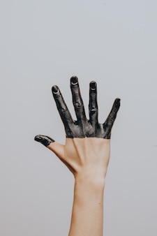 Elegant female hand dipped in black paint. isolated. gesture.