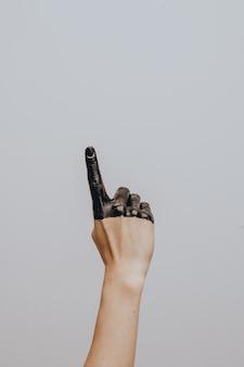 우아한 여성의 손을 검은 페인트에 담근. 외딴. 몸짓.
