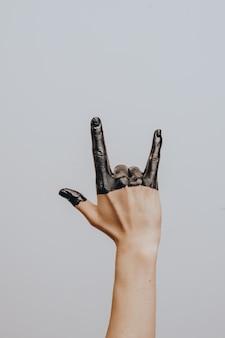 エレガントな女性の手は黒いペンキに浸しました。分離されました。ジェスチャー。