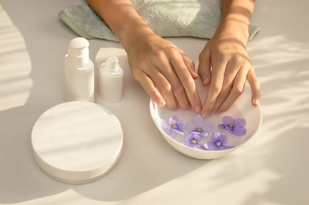 Elegant, female hands with long fingers. skin care procedure for nails, manicure. concept of spa beauty salon.