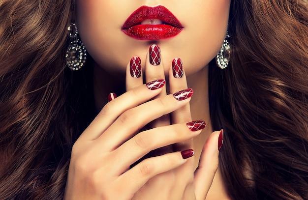爪にプロが作ったマニキュアをあしらったエレガントな女性の手。チェリーの口紅で彩られた形の良い唇の前にある美しく細く優雅な指。マニキュア、ジュエリー、化粧品。