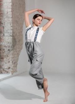エレガントな白いシャツとサスペンダーでスタジオで踊るエレガントな女性モデル。新しい女性らしさの概念