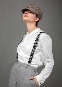エレガントな白いシャツとサスペンダーのエレガントな女性モデル。新しい女性らしさの概念