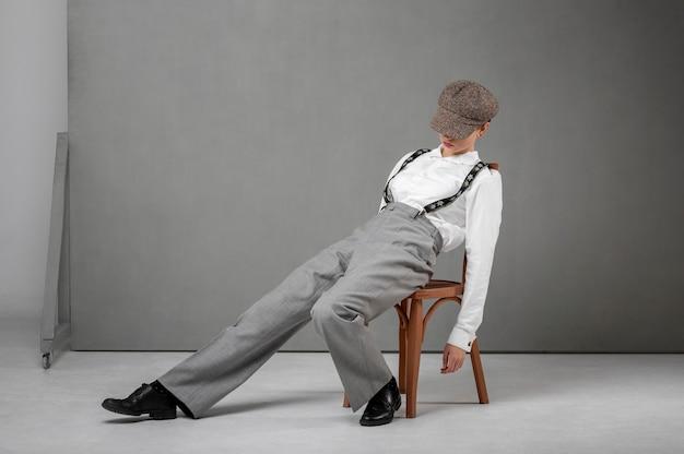 エレガントな白いシャツとサスペンダーの椅子でポーズをとるエレガントな女性モデル。新しい女性らしさの概念
