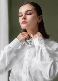 ネクタイとジャケットのスーツでポーズをとるエレガントな女性モデル。新しい女性らしさの概念