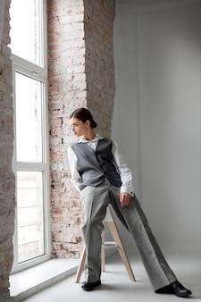 エレガントなチョッキの窓でポーズをとるエレガントな女性モデル。新しい女性らしさの概念