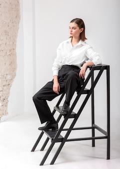 ジャケットスーツの階段でポーズをとるエレガントな女性モデル。新しい女性らしさの概念