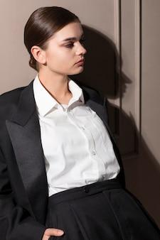 ジャケットスーツを着てスタジオでポーズをとるエレガントな女性モデル。新しい女性らしさの概念